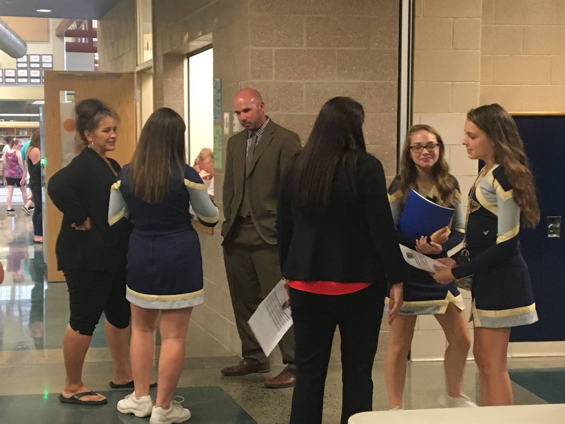 Cheerleaders meeting with school leaders during the open house