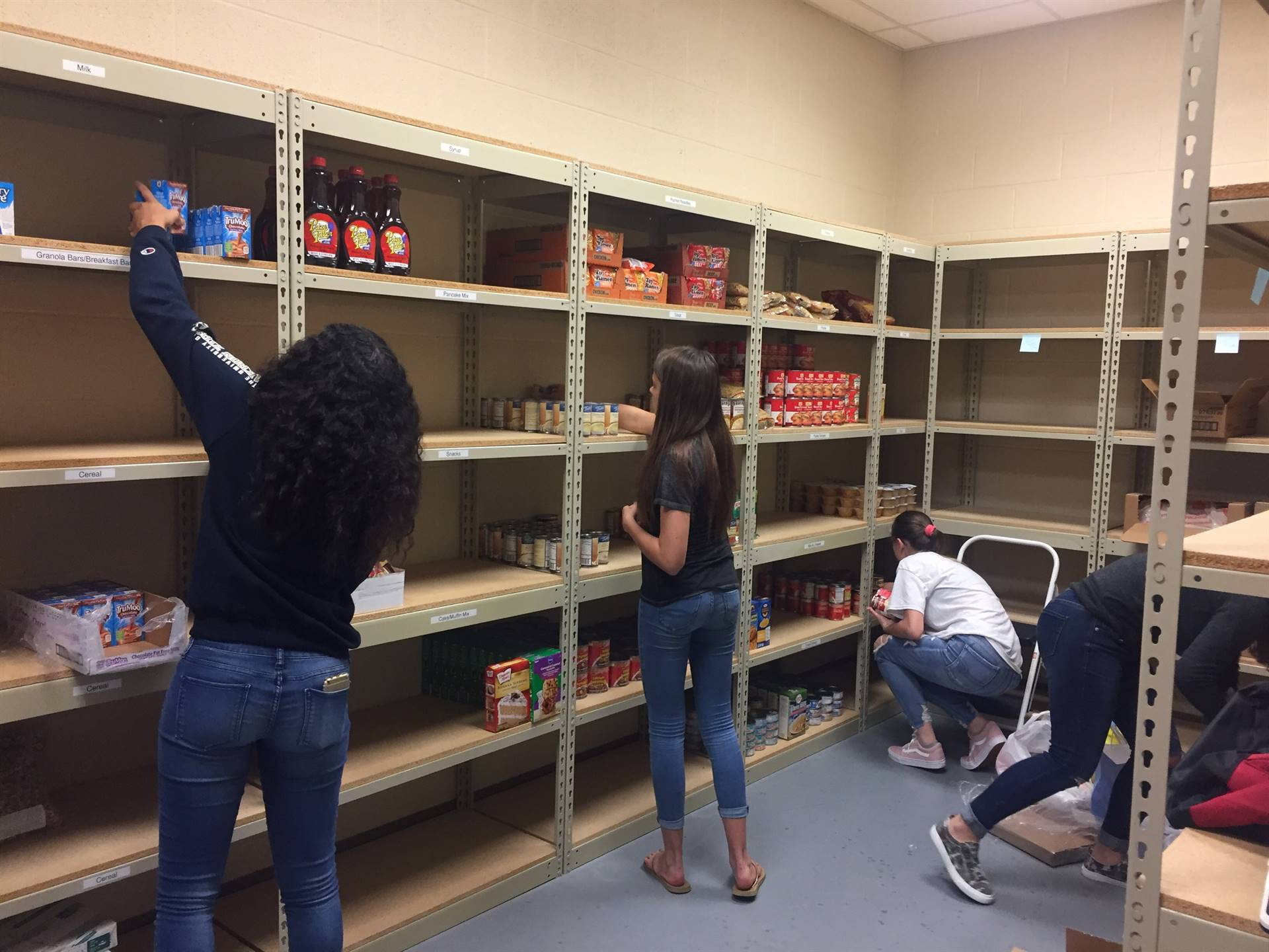 High School students stocking shelves in the Brookfield Middle School Warrior Pantry