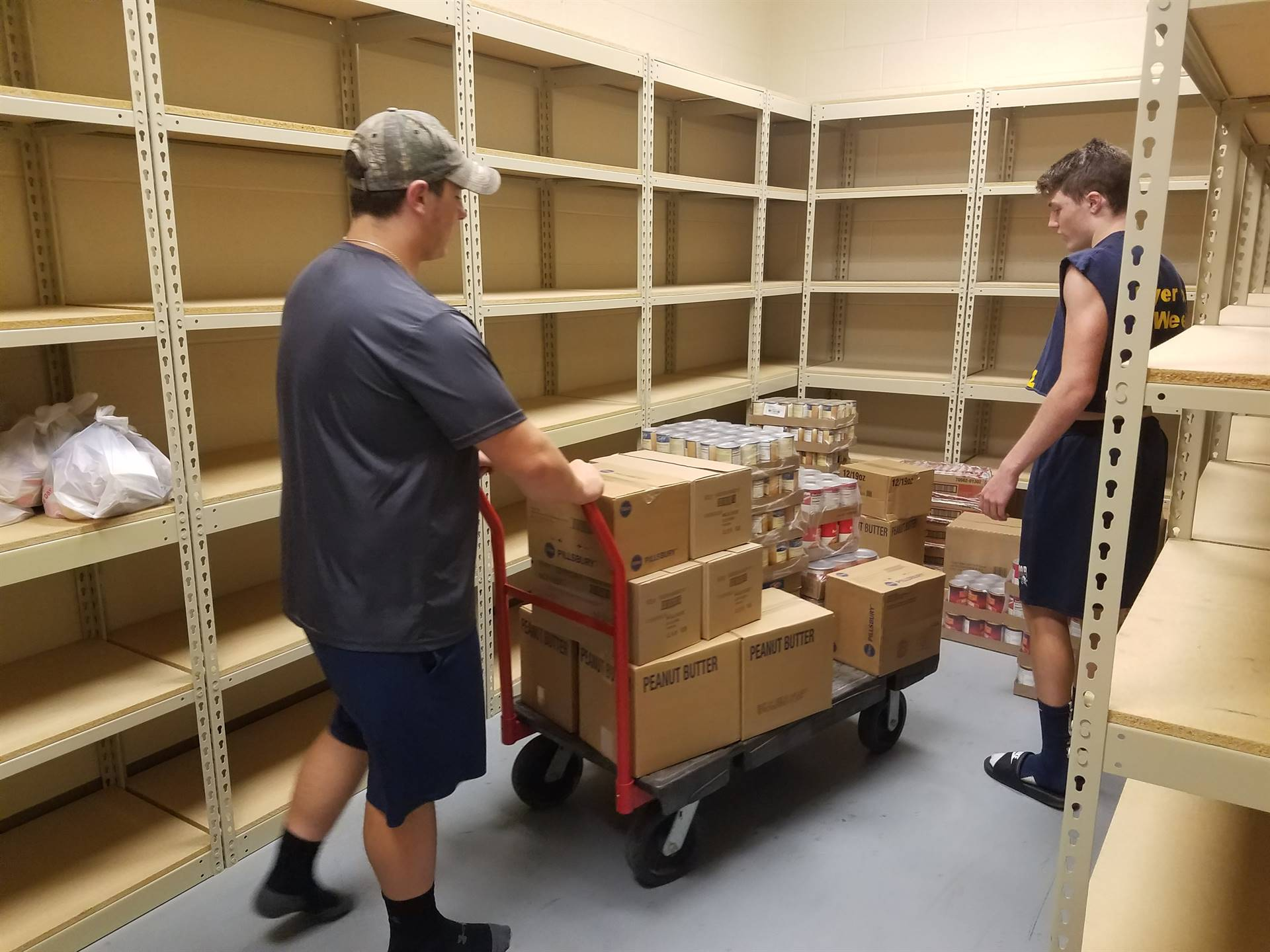Members of the High School football team unloading food from Second Harvest Food Bank for the Brookf